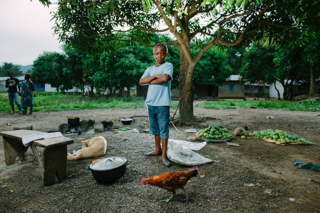 Feremusu Turay one of the Swawou School students infront of the cooking area next to her house. With her homework and all the mangoes she has just picked.
