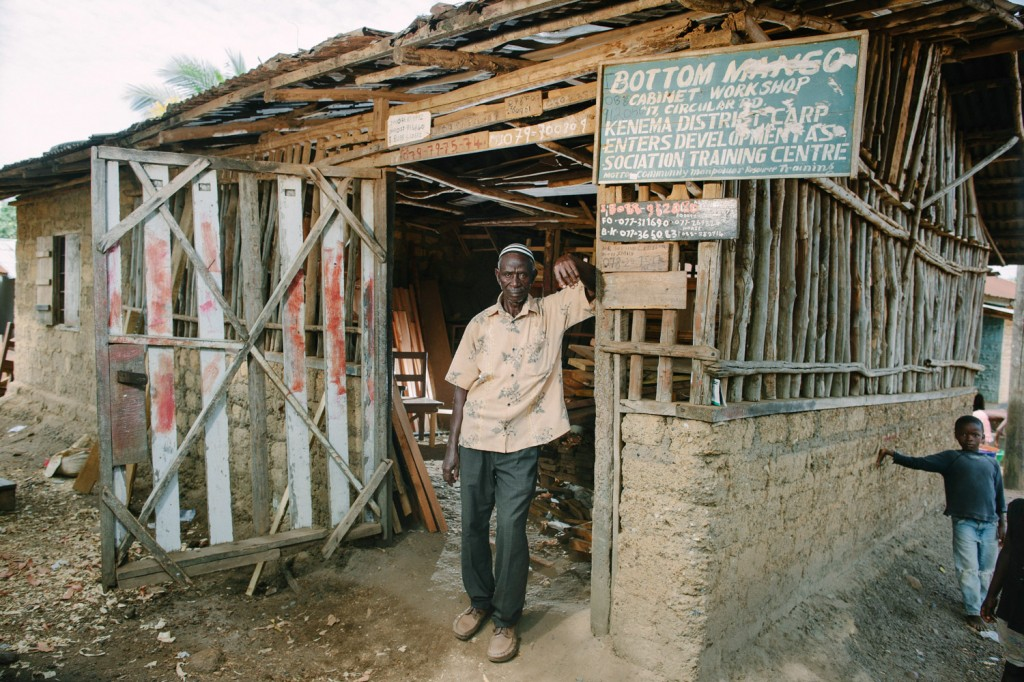 Musa Jaward in front of his wood store for his carpentary business. The workshop is out of the frame to the left under a huge mango tree